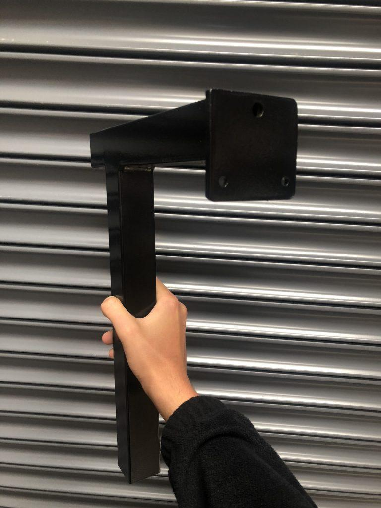 A black, zinc plated and black powder coated bench leg used in changing rooms/facilities for customers we manufacture for who operate in the leisure sector.